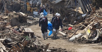 Rescue workers carry a bodybag through a devastated neighbourhood - Dan Chung for The Guardian (click for full coverage)